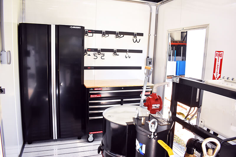 Interior of the fuel polishing trailer showing storage, workbench, fire extinguisher, waste oil drum, and more.